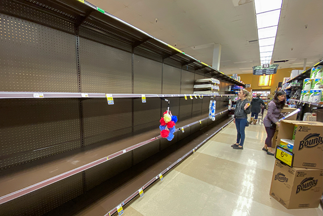 Shelves previously filled with toilet paper are seen empty at a Ralph's grocery store in Encinitas, California.