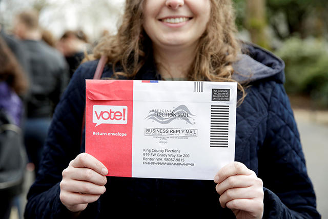 Lexi Menth of Seattle holds up her vote-by-mail ballot.