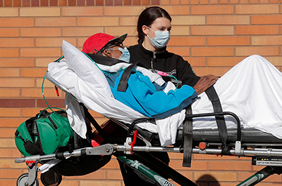 A healthcare worker wheels a patient on a stretcher