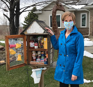 Robyn Floyd with her Little Free Library in Rochester.