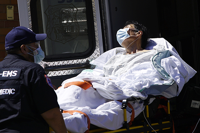A paramedic taking a patient from an ambulance to an emergency arrival area at Elmhurst Hospital in the Queens borough of New York City on Monday.