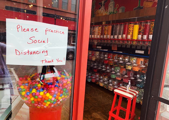 A sign and a sanitizer bottle: Tremblay's Sweet Shop, Stillwater.