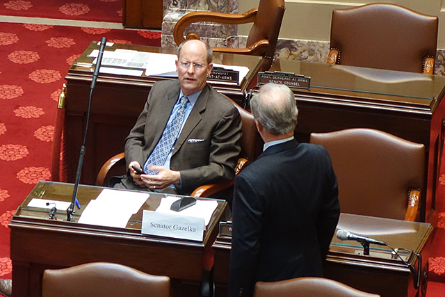 Senate Majority Leader Paul Gazelka speaking with Sen. Warren Limmer in close proximity on the Senate Floor.