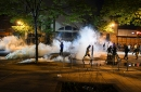 Protesters run from tear gas