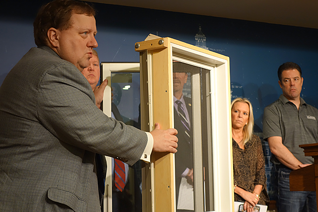 Darrell Dorr of Marvin Windows demonstrates a fall-prevention safety latch during a March press conference on housing regulations. Sen. Karin Housley, R-St. Marys Point, looks on.