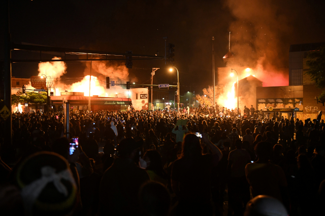 photo of protesters outside burning third precinct