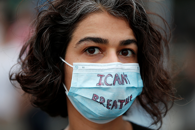 """A protest wearing a face mask with the words """"I can't breathe"""""""