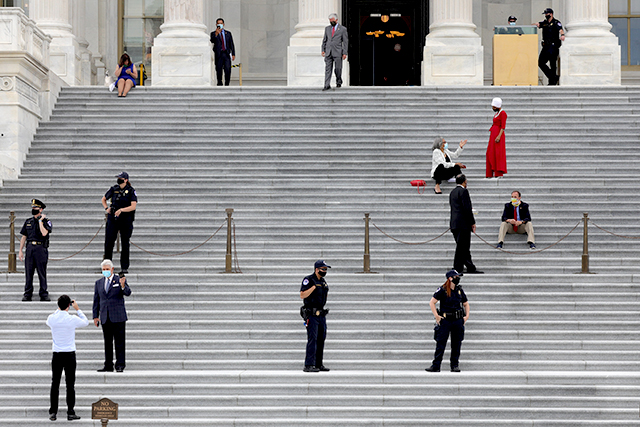 Capitol Police officers stand by as members of the U.S. House of Representatives commute to cast proxy votes for the first time in its 231-year history.