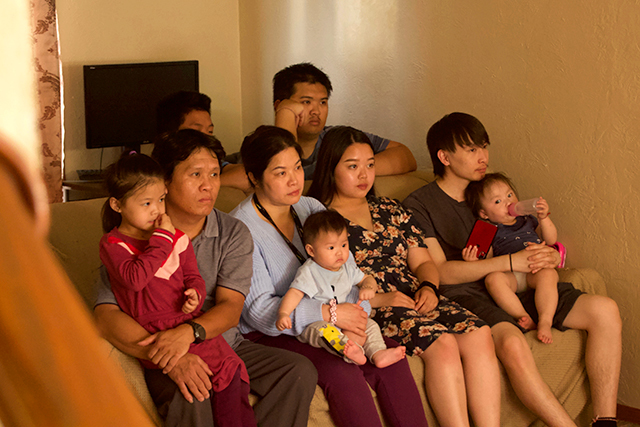 Bao Vang watching her Washington Technology Magnet School graduation ceremony, surrounded by family, in her living room on June 3. They gathered at 5:30 p.m. to livestream the ceremony, by connecting a laptop up to their TV.