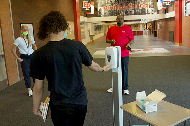 Upon entering Eden Prairie High School on June 4 to pick up his cap and gown, Troy Brown followed directions to put on a face mask and sanitize his hands. Staff had taped out a one-way path, winding through the building, for students to follow.