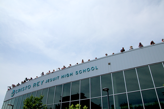 Teachers and staff lined up along the rooftop of Cristo Rey Jesuit High School to partake in a drive-through graduation ceremony held in front of the school building on June 6. Their view from the opposite side of the building included a burnt down AutoZone — a relic of the riots that followed the death of George Floyd.