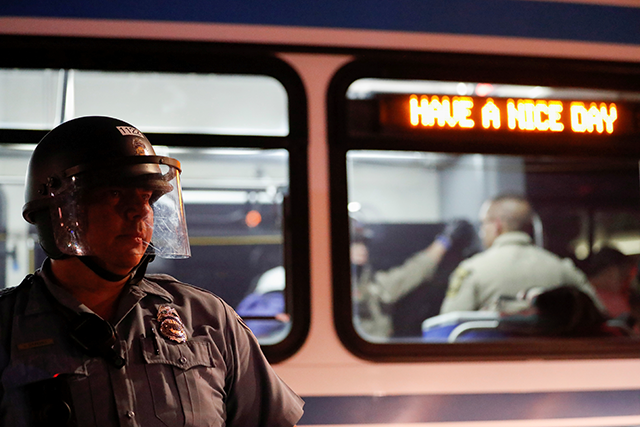 A police officer standing in front of a bus during a May 31 rally in Minneapolis.
