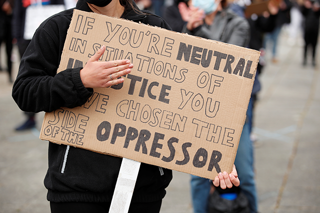 A demonstrator holding a placard during a Black Lives Matter protest in Station Square, in Milton Keynes, Britain, on June 6.