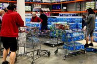 Customers loading shopping carts with toilet paper and water at a Costco store in Carlsbad, California, on March 2.