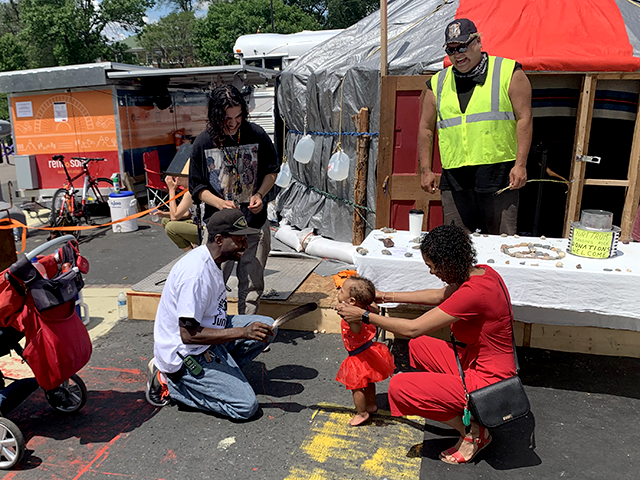 """'Sonic' and friends perform a smudge and feather ceremony for a young Juneteenth reveler at a yurt emblazoned with the words, """"This yurt came from Standing Rock, RIP George."""""""