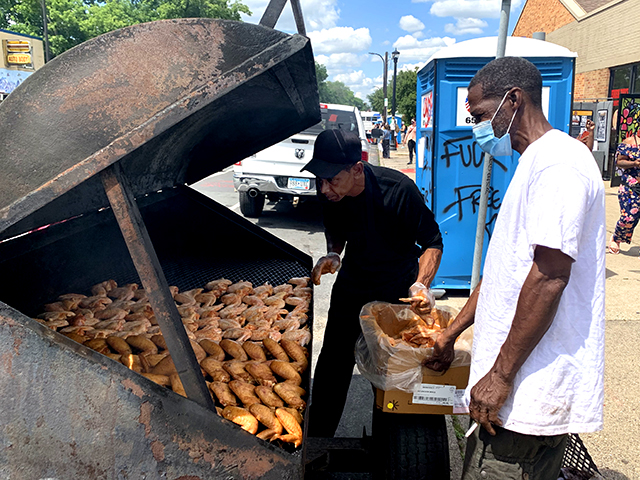"""""""I'm known for my smoked chicken wings"""": Smoke In The Pit Take Out owner Dwight Alexander fed the Juneteenth crowds."""