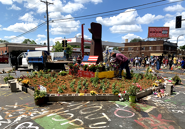 A gardener tended to the garden and bronze fist memorial that has sprung up on 38th and Chicago since May 25.