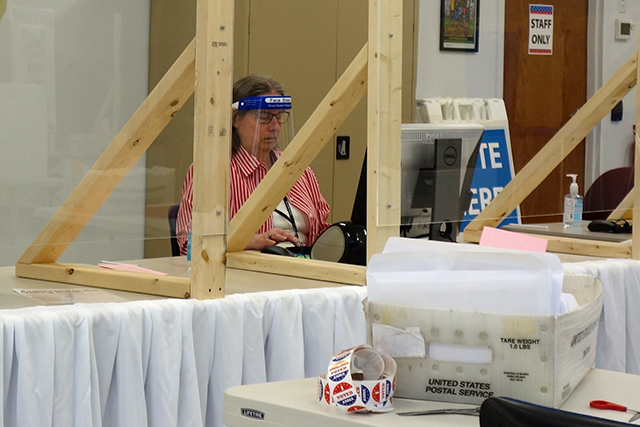 An election judge wearing personal protective equipment at the early voting center off East Hennepin Avenue in Minneapolis.