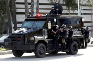 Police in riot gear on an armored vehicle