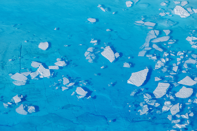 Chunks of ice float inside of meltwater pools on top of the Helheim glacier near Tasiilaq, Greenland.