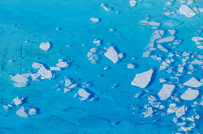 Chunks of ice float inside of meltwater pools on top of the Helheim glacier near Tasiilaq, Greenland.