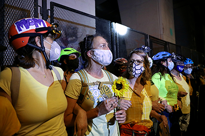 Mothers stand between federal law enforcement officers and protesters during a protest