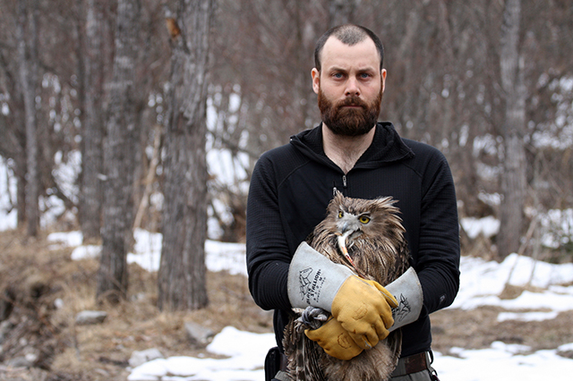 Jonathan Slaght with a Blakiston's fish owl. The owl is holding a trout in its beak.