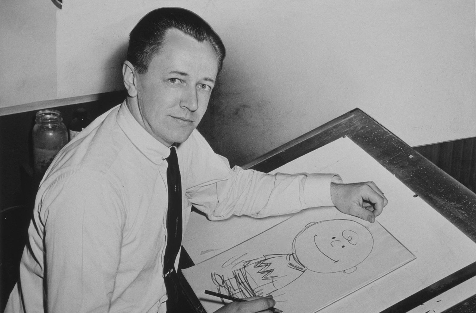 photo of charles schulz with a drawing of charlie brown