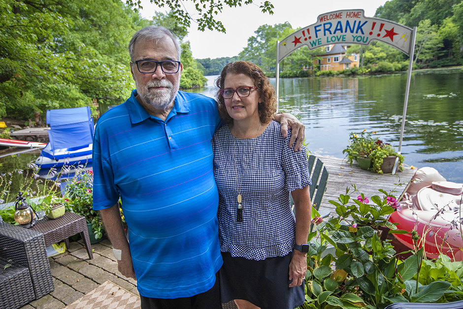 Frank and Leslie Cutitta standing outside their home in Wayland, Massachusetts, where a banner still hangs for his return from the hospital.