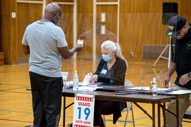 Elections officials check voters' IDs and distribute ballots at the polling place in the gymnasium of the Police Safety Academy in Milwaukee on Aug. 11, 2020.