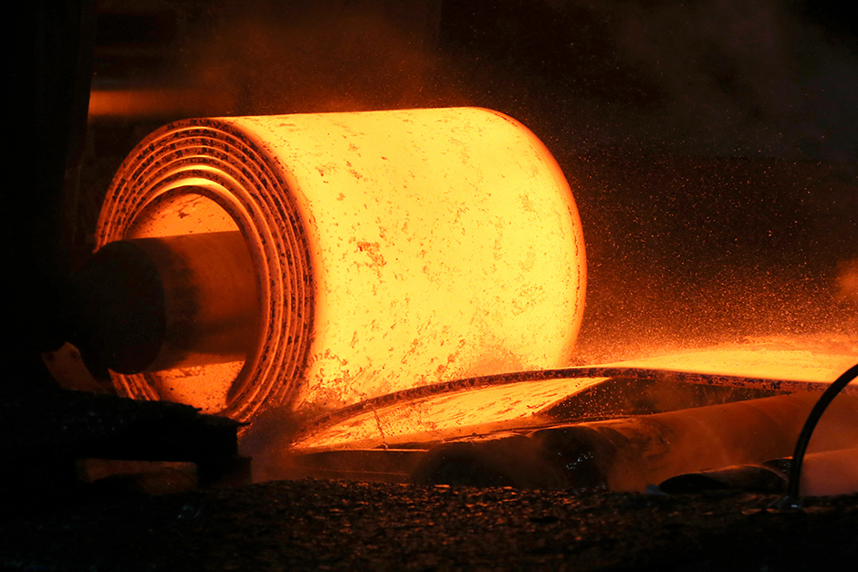 A steel coil is unrolled on the line