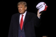 President Donald Trump holding MAGA hats