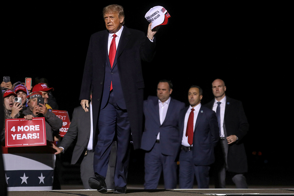 President Donald Trump holding MAGA hats during a campaign rally at Duluth International Airport on Wednesday.