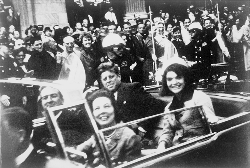 President John F. Kennedy pictured in the Dallas motorcade moments before being assassinated on November 22, 1963.