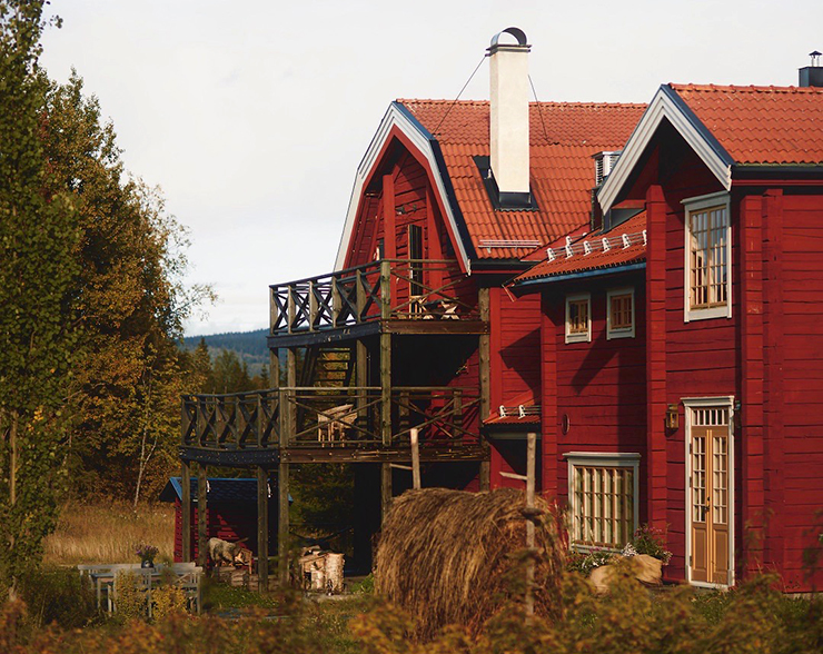 The restaurant Fäviken in late summer with hay drying in the wind on a traditional hay fence.