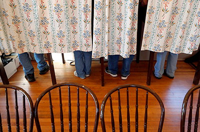 Voters standing behind a curtain at Florence Town Hall on Election Day in Frontenac, Minnesota.