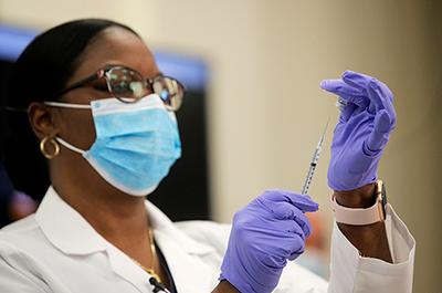 Dr. Michelle Chester preparing to administer a Pfizer coronavirus disease vaccine
