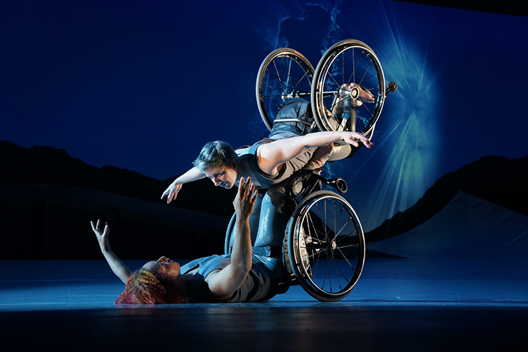 Laurel Lawson, a white woman, is flying in the air with arms spread wide, wheels spinning, and supported by Alice Sheppard. Alice, a light-skinned Black woman, is lifting from the ground below. They are making eye contact and smiling.
