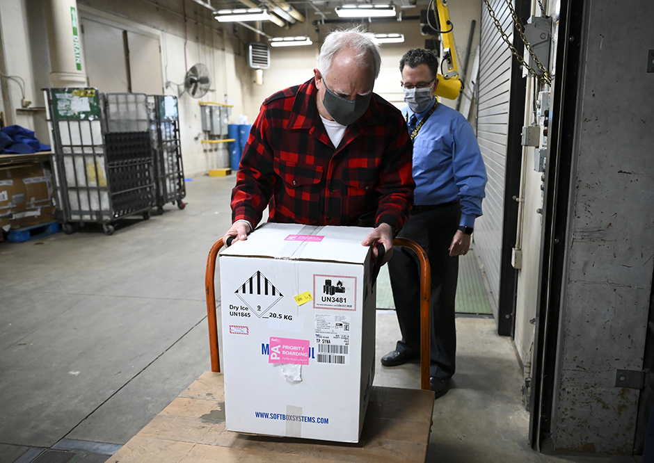 Gov. Tim Walz lifting the just-delivered box of 2,925 doses of the Pfizer COVID-19 vaccine on Monday morning.