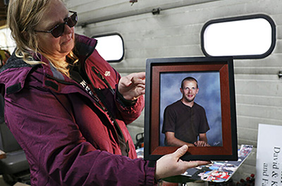 Amy Fischer is seen with a photo of her son, Brian