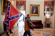 A supporter of President Donald Trump carrying a Confederate battle flag