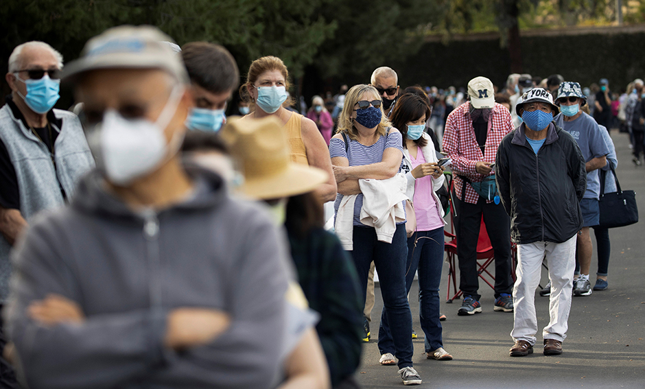 People waiting in line in a Disneyland parking lot to receive a dose of the Moderna COVID-19 at a mass vaccination site in Anaheim, California, on Wednesday.