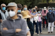 People waiting in line in a Disneyland parking lot to receive a dose of the Moderna vaccine at a mass vaccination site in Anaheim, California, on Wednesday.