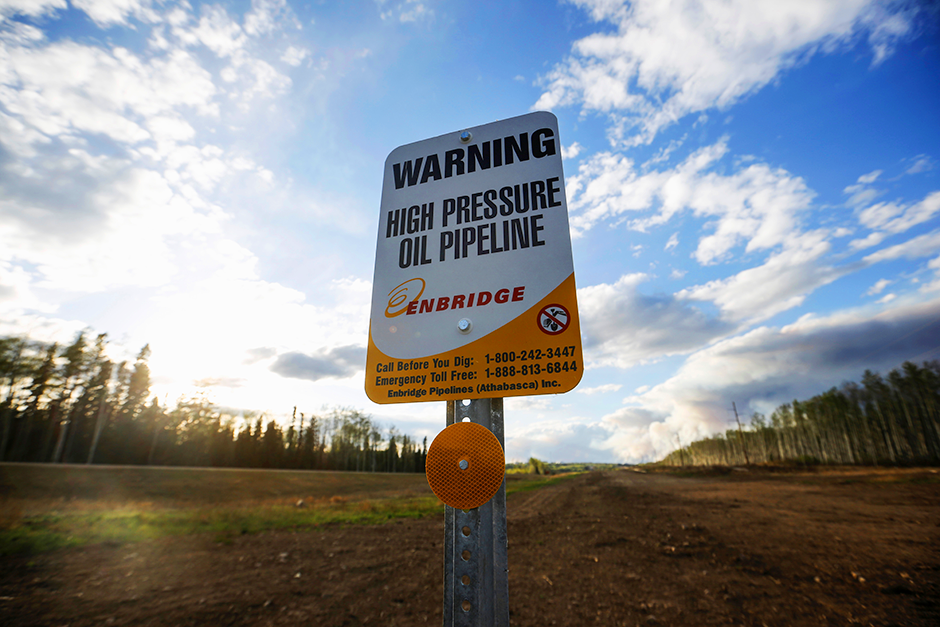An Enbridge high pressure oil pipeline sign standing near Kinosis, Alberta, Canada.