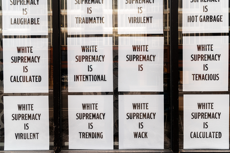"There's a poster printed with ""White Supremacy Is,"" the rest left blank for observers to complete."