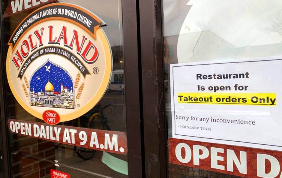 """A """"take-out only"""" sign on the front door of Holy Land bakery and restaurant in northeast Minneapolis."""
