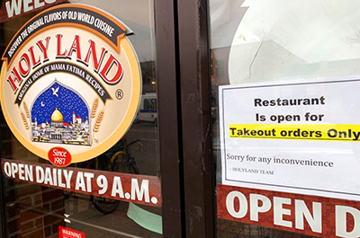 "A ""take-out only"" sign on the front door of Holy Land"