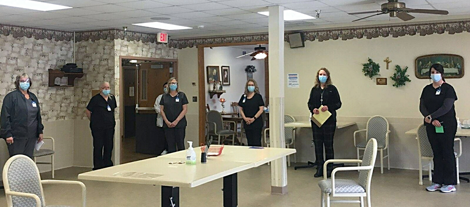 """The staff at CentraCare-Long Prairie Care Center, shown during a regular """"huddle"""" meeting, where managers meet with staff to discuss the upcoming work day, and provide tips for strengthening mental health."""