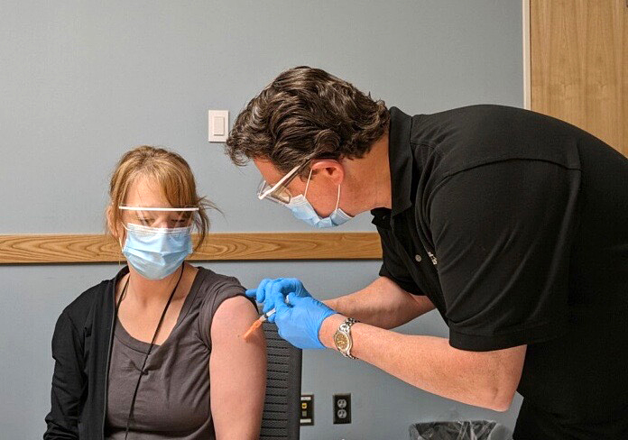 Steve Leslie administering a dose of the COVID-19 vaccine to Kelly Lind in Virginia, Minnesota. Both are public health nurse supervisors for St. Louis County.