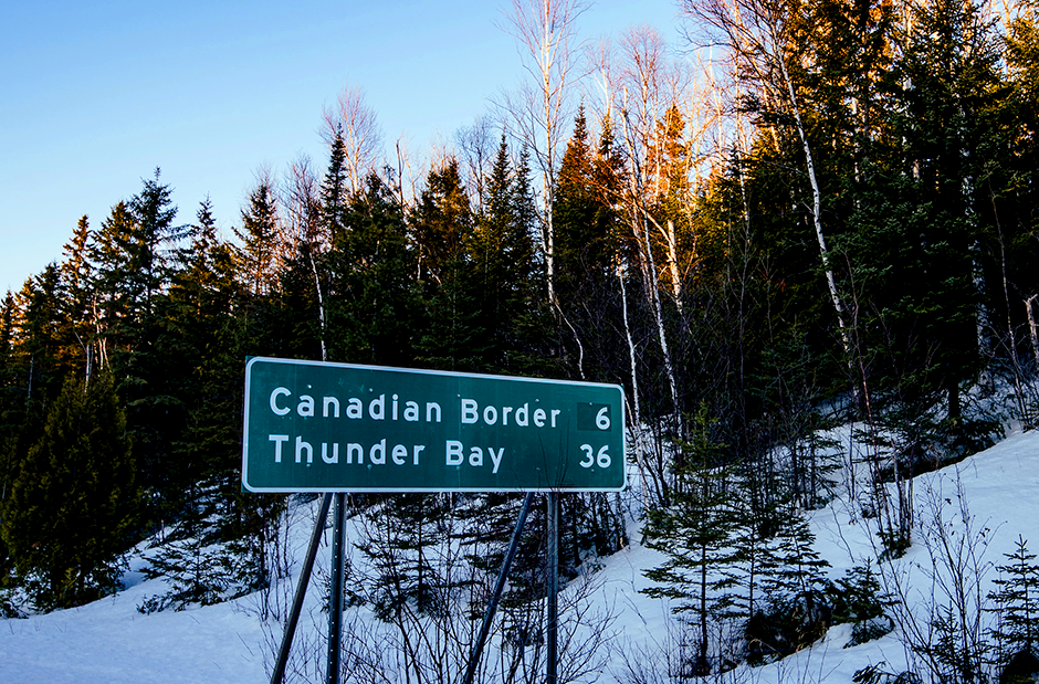 A sign along Highway 61 near Grand Portage showing the distance in miles to the Canadian border.